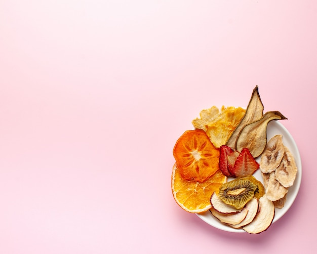 Dried fruit chips on a pink background.