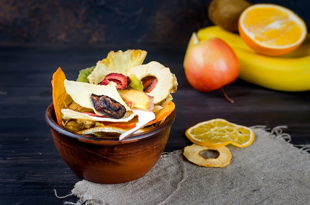 Dried fruit in plate on dark wooden background