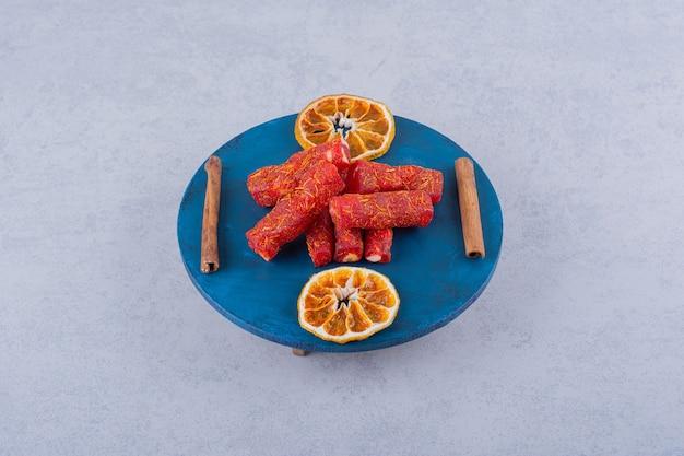 ブルーボードにナッツとシナモンスティックが入ったドライフルーツの果肉。