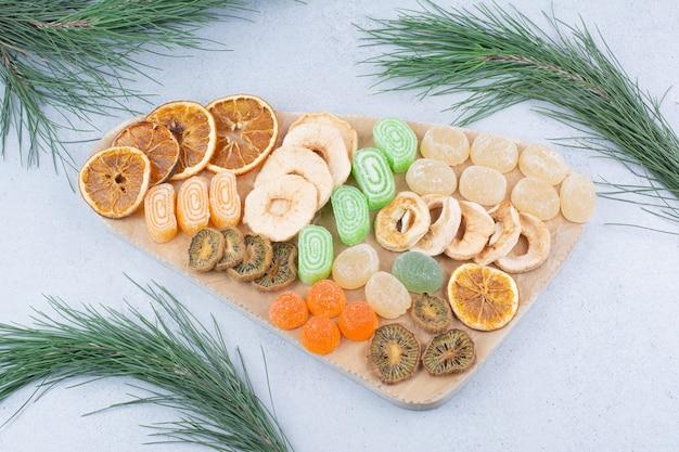 Ломтики сухофруктов и мармеладные конфеты на деревянной доске.