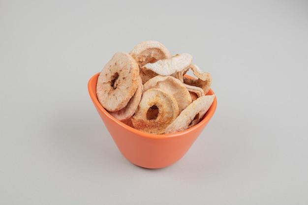 오렌지 그릇에 말린 과일 조각