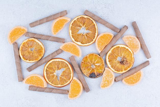 말린 과일 조각, 마멀레이드 및 대리석 표면에 스틱.