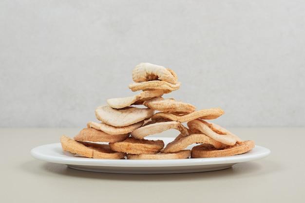 흰색 접시에 말린 과일 조각