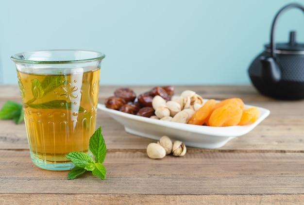 Поднос из сухофруктов с финиками, фисташками и курагой с чайным стаканом на деревянном дне. скопируйте пространство.