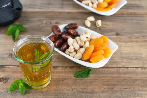 Dried fruit tray with dates, pistachios and dried apricots with tea glass on wooden bottom. copy space.
