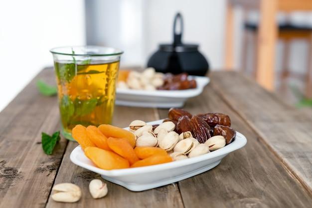 나무 배경에 차 유리가 있는 말린 과일 트레이. 공간을 복사합니다. 클로즈업 보기입니다. 음식.