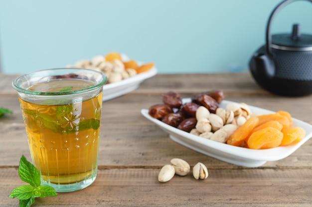 Поднос сухофруктов с стаканом чая на деревянной поверхности. скопируйте пространство. крупным планом. еда.