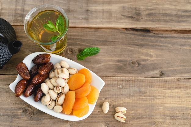 Dried fruit tray with tea glass on wooden background. copy space. top view.
