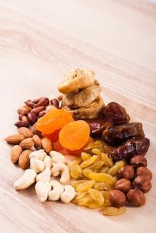 木製のテーブルにドライフルーツとナッツの山 Premium写真