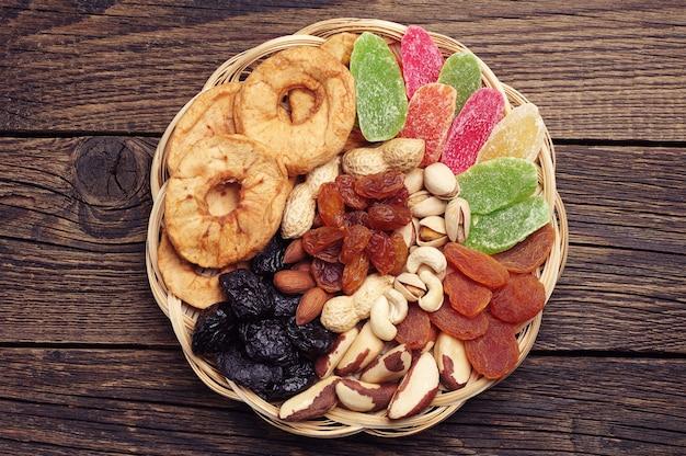 빈티지 나무 배경에 고리버들 그릇에 말린 과일과 견과류