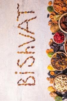 ドライフルーツとナッツを木製のボウルに混ぜる