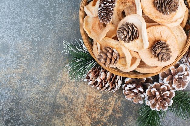 大理石の背景に木製のボウルにドライフルーツと松ぼっくり。高品質の写真