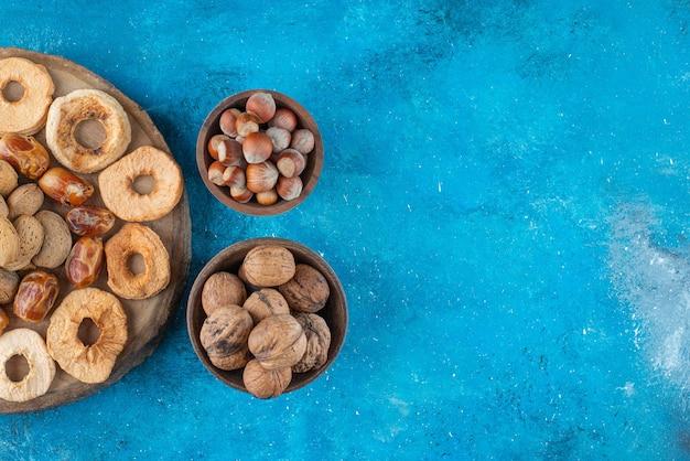 Сухофрукты и вкусные орехи на доске, на синем столе.