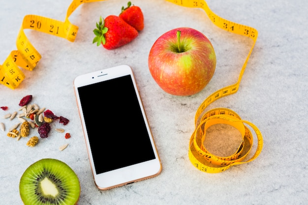 Dried fruits; apple; halved kiwi; strawberry; measuring tape and smartphone on gray textured background