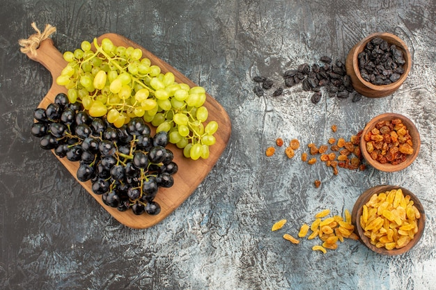 Dried fruits bunches of green and black grapes on the board and dried fruits