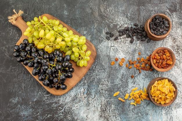 ボード上の緑と黒のブドウのドライフルーツの束とドライフルーツ