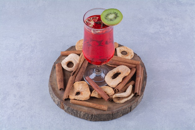 Dried fruits, cinnamon stick and cherry juice on a board , on the marble table.