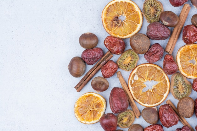 Frutta secca, bastoncini di cannella e castagna sulla superficie in marmo.