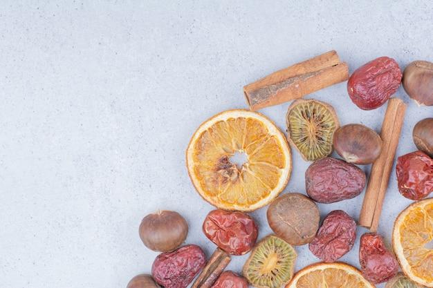 Frutta secca, bastoncini di cannella e castagne sulla superficie in marmo.