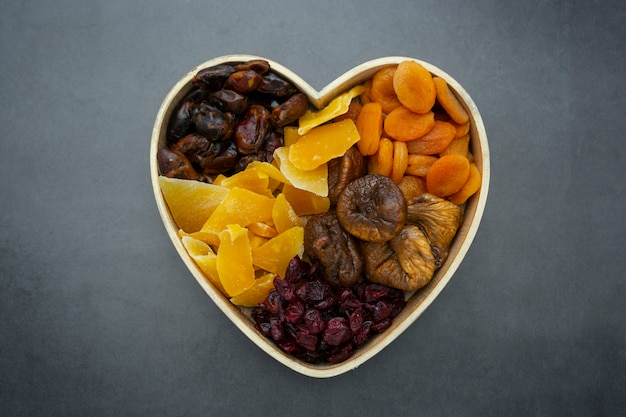 Dried fruits mix, in wooden heart shape box isolated on dark background.