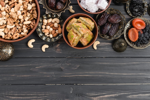 Dried fruits; nuts; dates; lukum and baklava on ramadan over the wooden desk