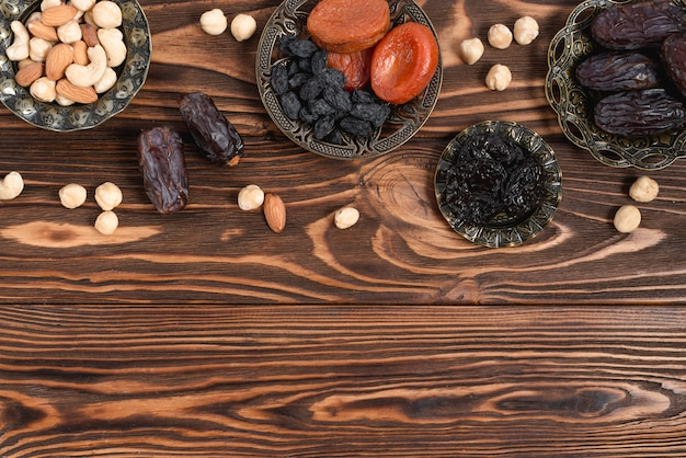 Dried fruits; nuts and fresh dates on wooden texture table