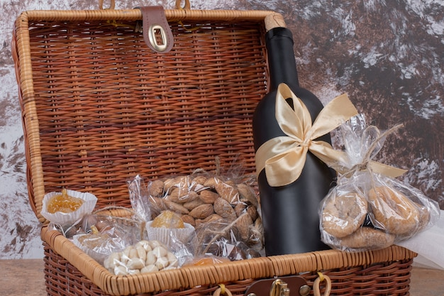 Dried fruits and nuts packed in plastic bags with wooden bag with bottle of wine.