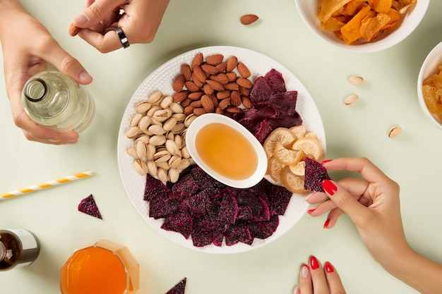 Dried fruits and nuts with sauce on green background with hands