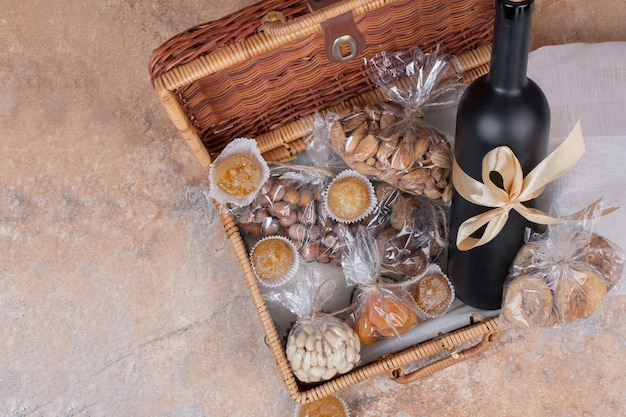 Dried fruits and nuts in wooden bag with bottle of wine.