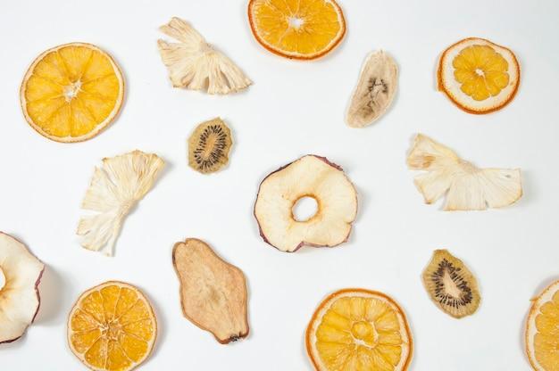 Сухофрукты апельсина, банана, яблока, киви, ананаса и груши на белом фоне вид сверху