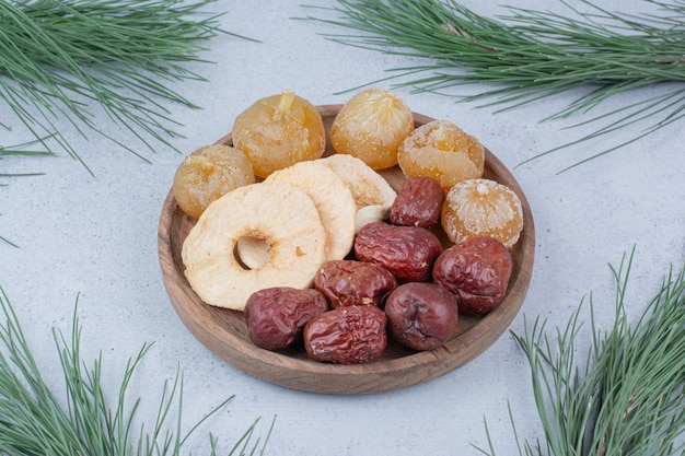 Dried fruits and oleaster on wooden plate.