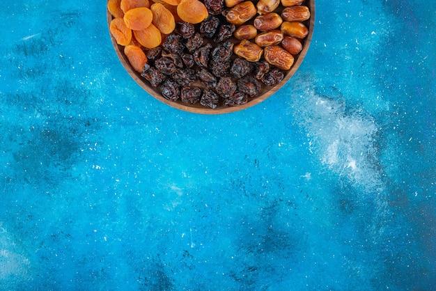 Сухофрукты на доске, на синем столе.