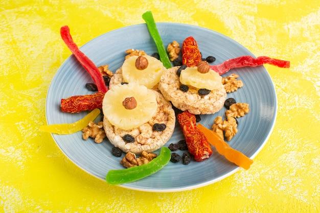 Anelli di ananas frutta secca noci e torrone all'interno del piatto blu su giallo