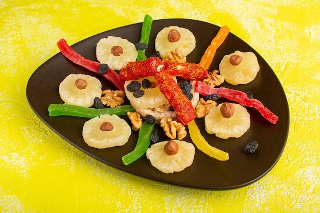 Ananas frutta secca anelli noci e torrone all'interno della piastra su giallo