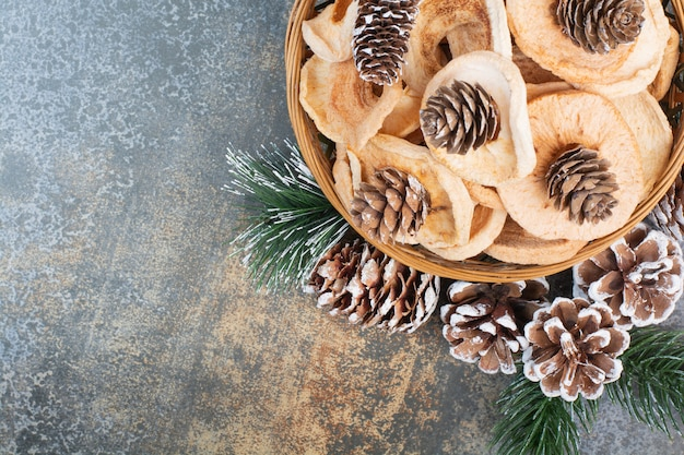 Dried fruits and pinecones in wooden bowl on marble background.high quality photo