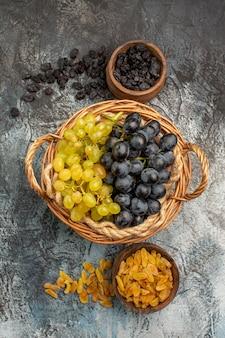 ドライフルーツのボウルの横にある食欲をそそるブドウ