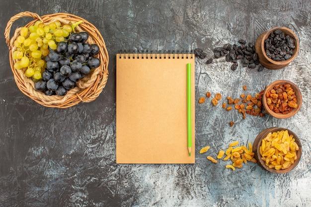 말린 과일 녹색과 검은색 포도 바구니 공책 연필 말린 과일