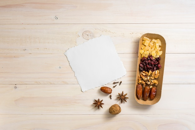 Dried fruits with walnuts and blank paper sheet