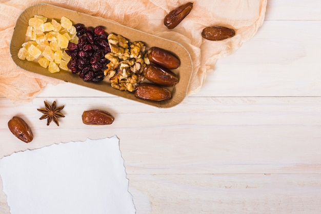 Dried fruits with walnuts and blank paper