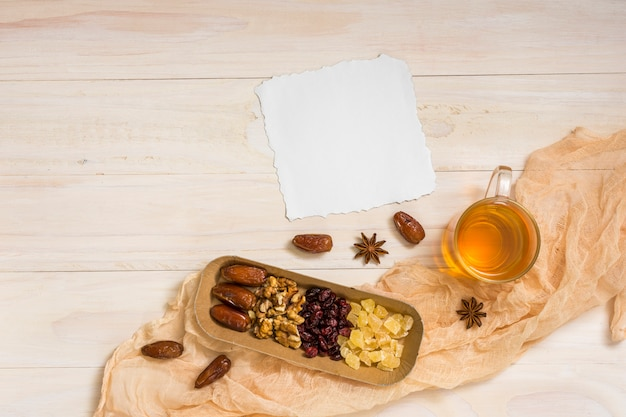 Dried fruits with walnuts, paper and tea