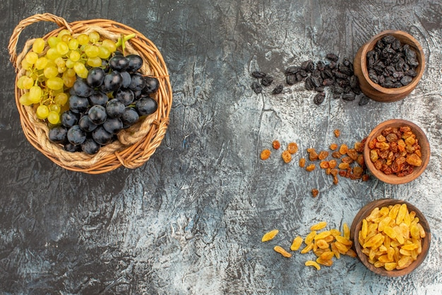 Dried fruits wooden basket of green and black grapes and dried fruits in bowls