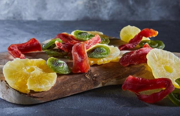 ドライフルーツ:灰色のコンクリートの木製まな板に黄色い砂糖漬けのパイナップルリング、赤いパパイヤ、緑のキウイ