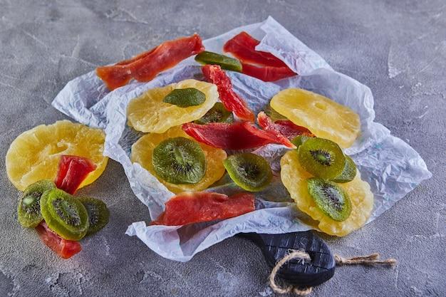 ドライフルーツ:灰色のコンクリートの白い包装紙に黄色い砂糖漬けのパイナップルリング、赤いパパイヤ、緑のキウイ