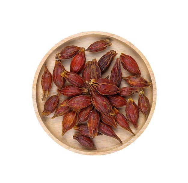 흰색 배경에 격리된 나무 접시에 말린 치자나무 열매.