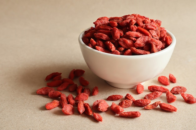 Dried goji berries in a white ceramic cup on brown