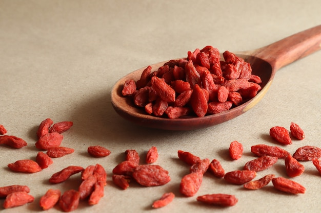 Dried goji berries in a wooden spoon on a brown background