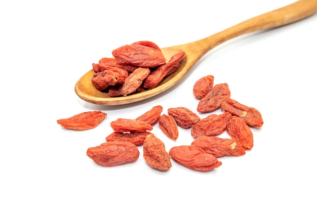 Dried goji berries in a wooden spoon