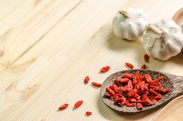 Dried goji berries on wooden tablespoon