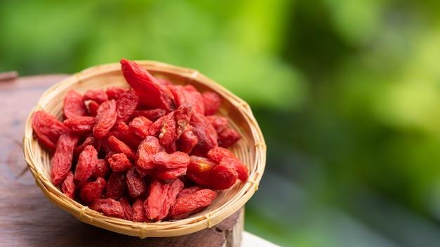 Сушеные ягоды годжи в бамбуковой корзине на фоне природы.