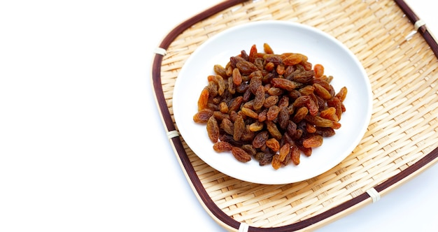 Dried grape raisins in plate on white background